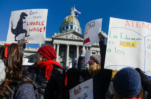 Teachers in Denver, Colorado are dressed in winter gear as they strike and hold large white signs in front of the Colorado State Capitol on February 11, 2019.