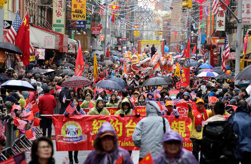 Asian revelers march among red and yellow and white and blue decorations hanging from grey and brown city buildings