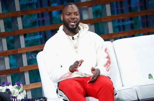 Martellus Bennett. Black man in white hoodie and red pants speaks while seated on white couch in front of blue background and brown slats