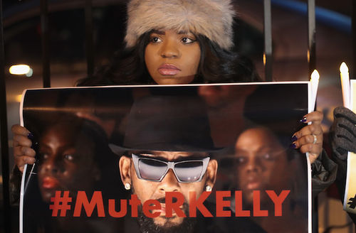 R. Kelly. Black woman in grey hat holds sign depicting Black man in black hat and shirt and sunglasses in front of nighttime sky.