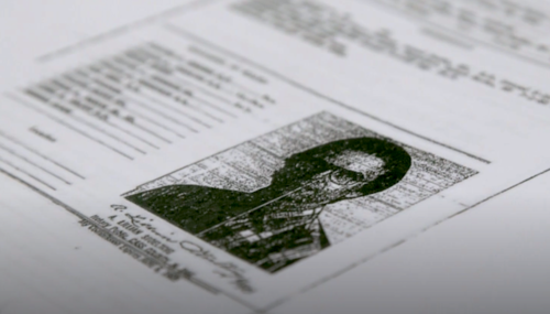 A document with the blurred face of an elderly White man and type