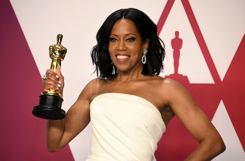 Regina King. Black woman with black hair in beige dress smiles and poses while holding gold Oscar statuette on black pedestal in front of red and white background.