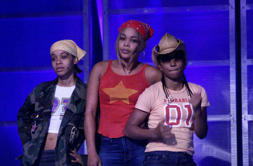 """Lisa """"Left Eye"""" Lopes, T-Boz and Chilli of TLC. Black woman in yellow bandana and camouflage jacket next to Black woman in red bandana and shirt next to Black woman in coral shirt and brown hat in front of blue screen."""