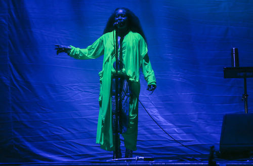 A Black woman with long hair wearing a neon green jacket performs onstage in front of a blue background.
