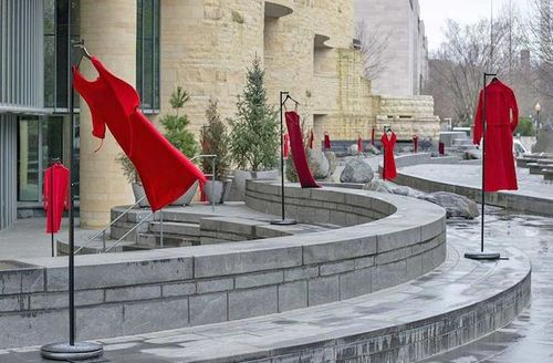 Red dresses hang from poles in a concrete sitting area outside of a concrete building.