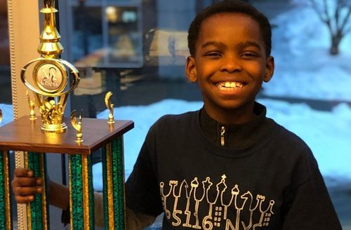 A young Black Boy in a black shweatshire smiles while holding a large gold and green trophy in his right hand.