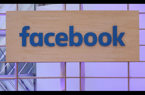 """Blue text spells """"Facebook"""" on brown wood sign in front of purple lights and metal frames"""
