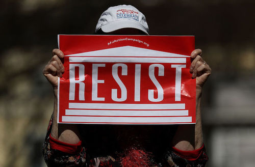 """woman holding protest sign that reads """"Resist"""" in Washington, D.C."""