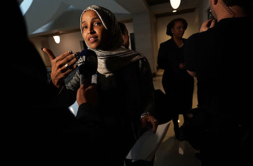 Black woman in headscarf, Ilhan Omar, speaks into a microphone as she is questioned by press far in the background Black woman with hair tied, Ayanna Pressley, back speaks to press
