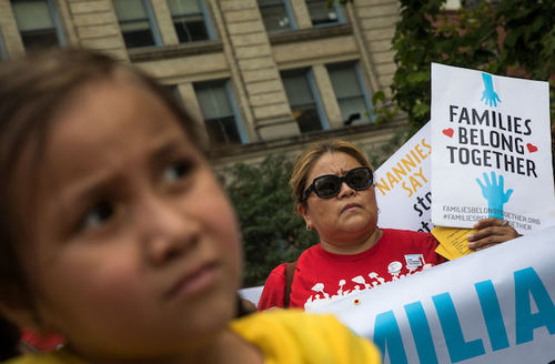 A small girl wearing a yellow shirt stands in front of a woman wearing a red shirt and holding a sign that says families belong together. They are protesting the Trump administrations family detention and separation policies for migrants along the souther