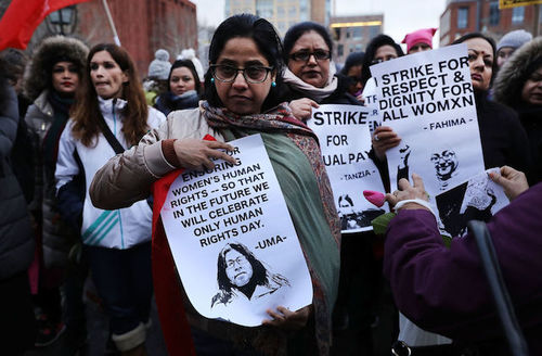 """Women stand outside, hold signts that read, """"I strike for respect and dignity for all womxn."""""""