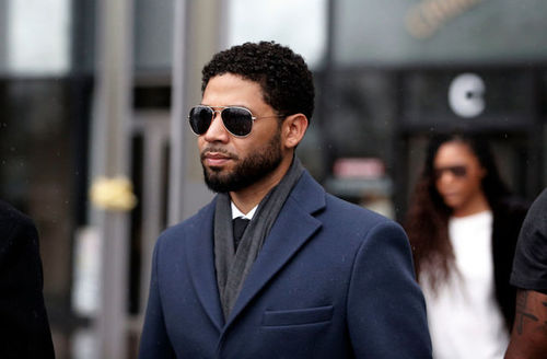 A Black man turned tot he side wearing a blue blazer and black sunglasses with a light beard stands in front