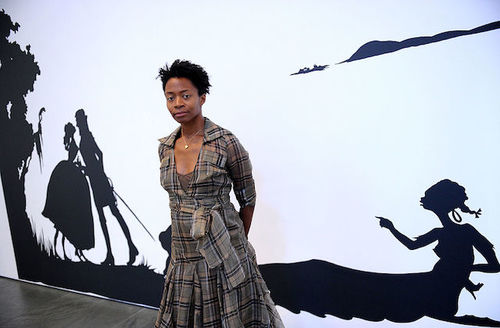 A young black woman with short hairs wears a plaid wraparound dress and stands in front of an art installation consisting of a white wall with black cutout characters transposed against it.