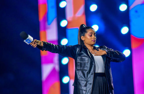Indian Woman with straight long hair in high ponytail stands on a stage in front of bright multicolored background wearing black leather jacket with one hand on her chest and another hand holding microphone towards an audience.