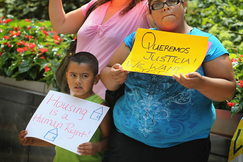 """A Latinx boy, Daniel on the left, and his mother, Virginia on the right, stand side-by-side at a rally held outside holding posters. Daniel's sign is white and says """"housing is a right."""" Virginia's is yellow and says, """"Queremos Justicia! We want justice."""""""