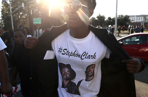 A Black man wearing sunglasses wears a white T-shirt with a with a photo of Stephon Clark during a demonstration in Sacramento, California on March 22, 2018.