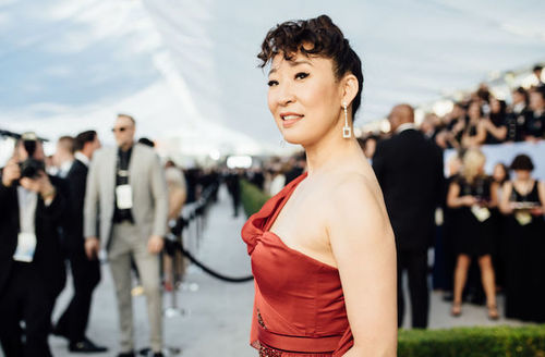 Asian woman with hair up and bangs wearing a read gown with shoulders exposed turned to the side and a crowd of red carpet reporters behind her.