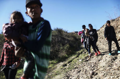 A is man wearing a striped shirt as he carries a child from and they descend a hill, just before crossing the U.S.-Mexico border fence and turning themselves in to the U.S. Border Patrol, on December 16, 2018.