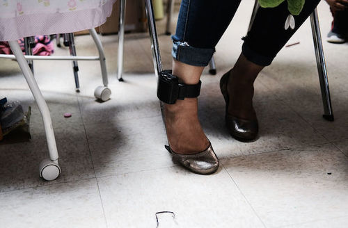 A woman's leg wearing an ankle monitor underneath a table with gold colored slippers