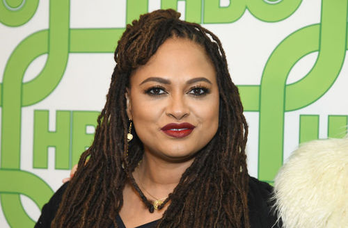 Ava DuVernay. A Black woman with long hair stands in front of a green and white background wearing red lipstick.