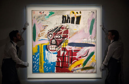 Jean-Michel Basquiat art of colorful skull head and two workers holding painting on each side.
