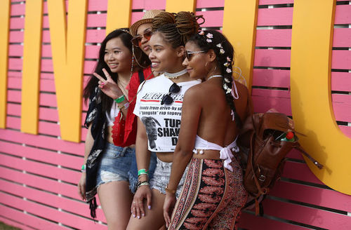 Three smiling young women of color pose side by side in front of a wall at the COachella music festival in 2018.