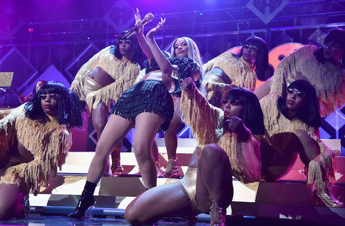 A Black woman on stage with many black dancers and back-up singers surrounding her.