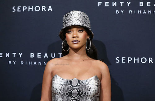 """Rihanna. A Black woman stands against a black wall that reads """"Sephora"""" in white letters, while wearing a gray and black snakeprint dress and matching hat."""