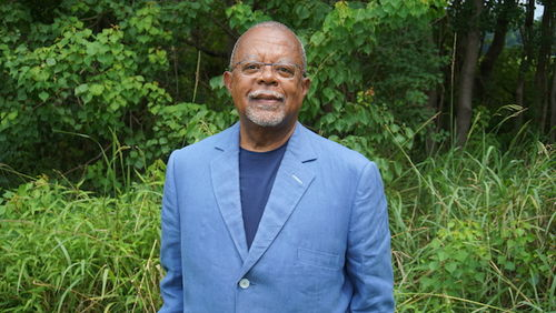 Henry Louis Gates Jr. A Black man with a blue jacket and gray beard stands outside with green lawn behind him.