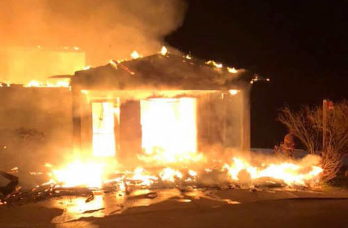 image of a a building set ablaze at night time