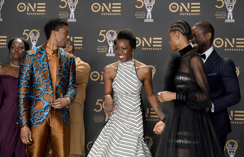 Six Black Men and Women stand next to each other on stage laughing after winning award, TVOne signage behind them.