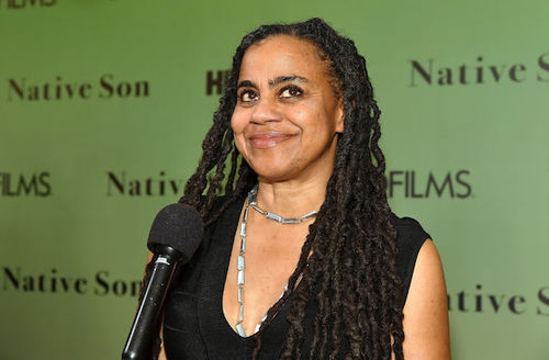 "A Black Woman with long hair and black shirt stands at event in front of wall that reads ""Native Son'."""