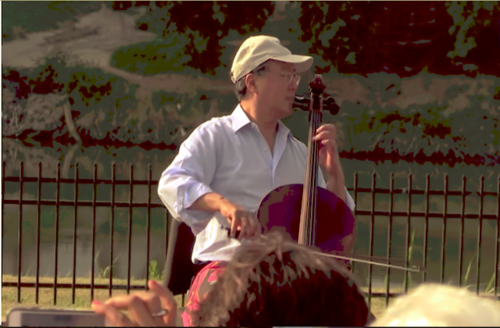 Asian Man with glasses and white baseball hat plays the cello with a brige and body of water behind him.