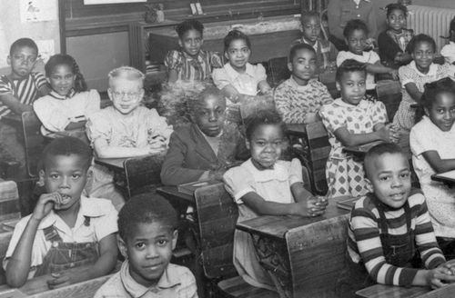 Shining little Black faces look at the camera as childen sit at wooden desks in a classroom. Photo is black and white.