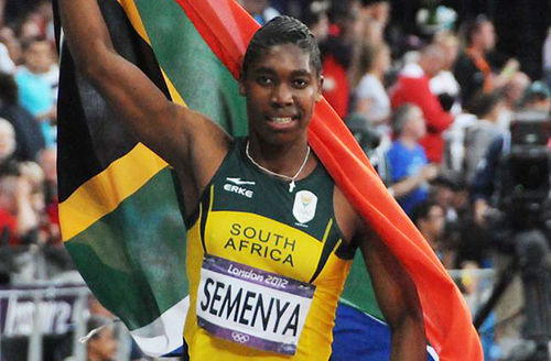 Caster Semenya. Braids, green and yellow jersey top. South African flag. Track.