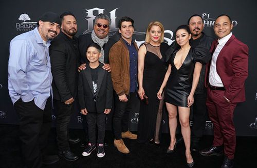 """Cast of """"Le Chicano."""" Nine people stand in a line in front of black backdrop"""