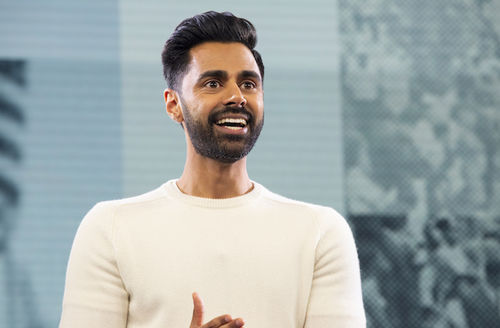 Hasan Minhaj. South Asian man with black hair and beard smiles while wearing white shirt in front of blue and teal background