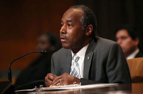 Ben Carson. Black man in black suit and white shirt sitting leans into tiny microphone