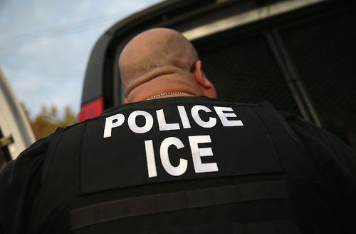 Close-up of the back of an agent wearing a black jacket with the words police ICE written in large, white letters.