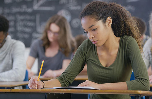 Black young woman with long ponytail and green top sitting at a brown table taking test in classroom.