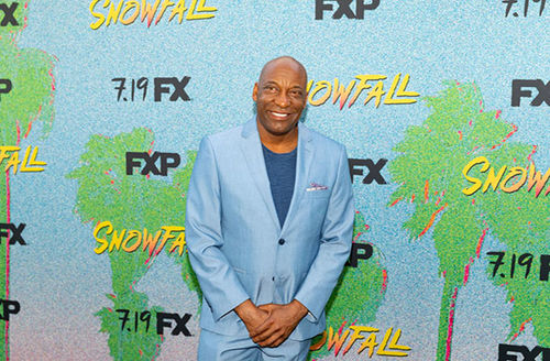 """John Singleton. Bald Black man in light blue suit in front of """"Snowfall"""" step and repeat."""