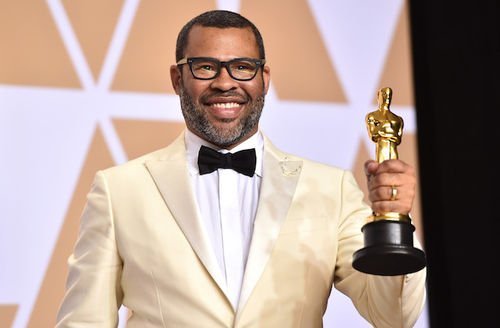 Black man in white tuxedo and black glasses smiles while holding gold award statue in front of black and white and gold background