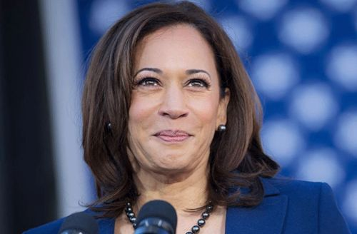 Kamala Harris. Black woman with straight shoulder-length hair wearing blue jacket in front of microphone.