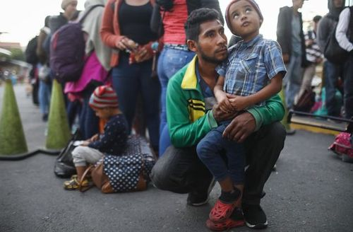 A Honduran father holds his son as they wait in line to cross the Guatemala-Mexico border and register at an immigration facility in Tecun Uman, Guatemala, on January 19, 2019.