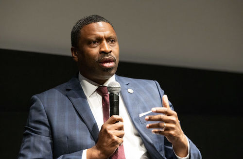 Derrick Johnson. A Black man wears a blue stripped suit, maroon tie and white shirt. He holds a black microphone.