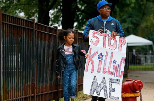 """a young Black girl with ponytails, blue overalls and a black biker jacket, walks with an older man wearing a blue baseball cap and a black and blue tracksuit. The man holds a sign that reads, """"stop killing me"""""""