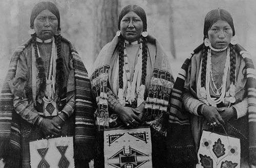 Three Native American women, standing, full-length, facing front, holding beaded(?) bags, Warm Springs Indian Reservation, Wasco County, Oregon.