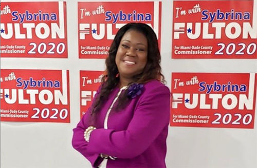Sybrina Fulton 2019. Black woman with long straight hair wearing purple jacket in front of campaign ads.