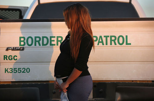 Profile view of pregnant woman wearing black shirt with long brown hair hiding her face standing beside a white and green U.S. Border Patrol truck.
