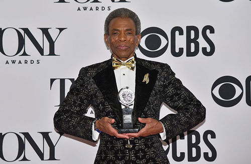 Andre De Shields. Older Black man with gray hair wearing black tux holding Tony award.